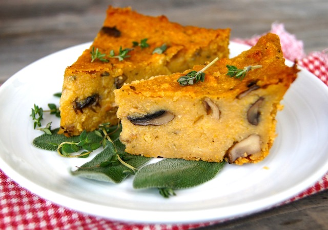 2 slices of Savory Polenta Cake with Mushrooms on a white plate on a wood table.