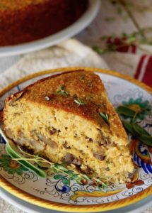 One slice of savory polenta cake with fresh herbs on decorative Italian plat