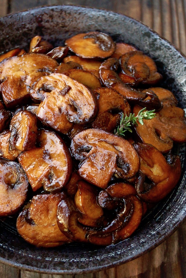 close up of browned mushroom slices in a black bowl with sprig of thyme
