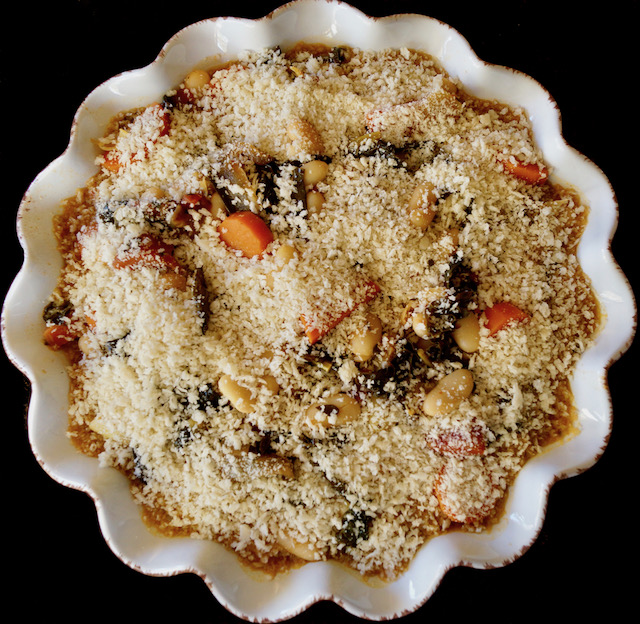 Vegetarian Cassoulet with breadcrumbs on top ready to go in the oven, in white pie dish.