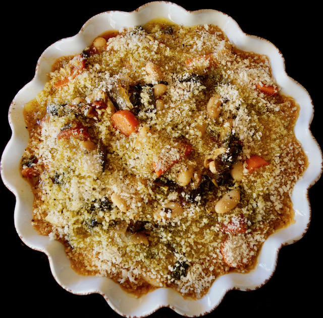 Vegetarian Cassoulet with breadcrumbs and olive oil on top ready to go in the oven, in white pie dish.