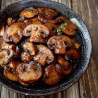 browned mushrooms in black bowl on wood surface
