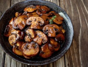 browned mushrooms in black bowl on wood surface