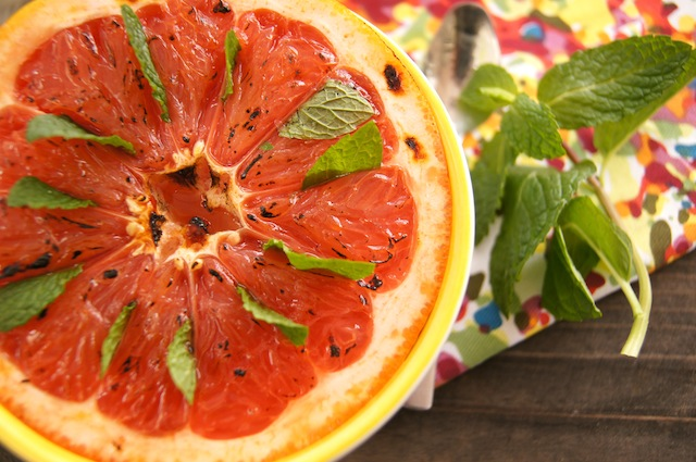 close up of half of a grapefruit with a mint leaf between each segment