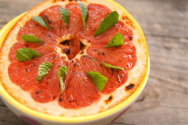 half of a Minty Grapefruit Brûlée in a yellow-rimmed bowl with mint leaves.