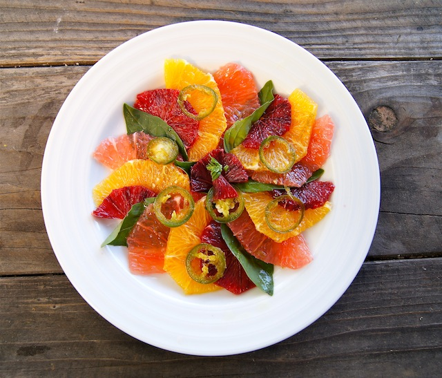 Winter Citrus Carpaccio in red, orange and picn, on a white plate.