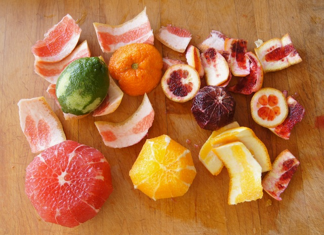 Peeled grapefruit and oranges and whole limes and orange and peels surrounding them.