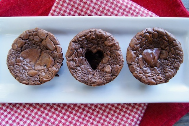 three Valentine's Day Nutella Brownies on a white plate showing the different stages of cutting/filling the heart shape