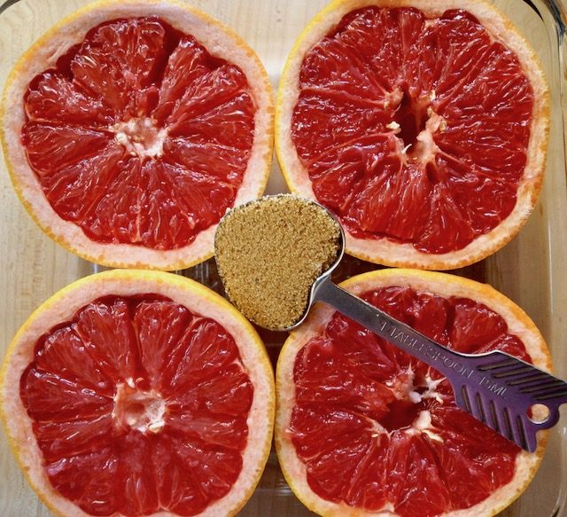four grapefruit halves with heart-shaped measuring spoon with brown sugar