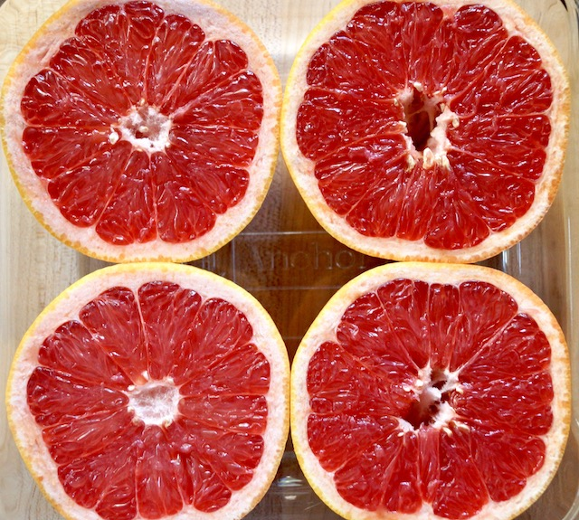 Four Ruby Red grapefruit halves in glass baking dish