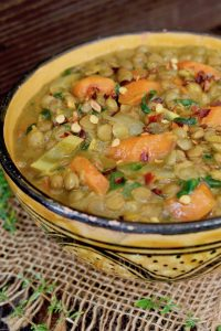 painted gold and black ceramic bowl with vegan lentil stew with carrots and coconut milk
