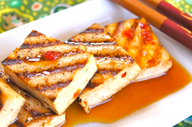 Grilled Tofu in Spicy Tangerine Marinade on a narrow white plate on a green cloth.