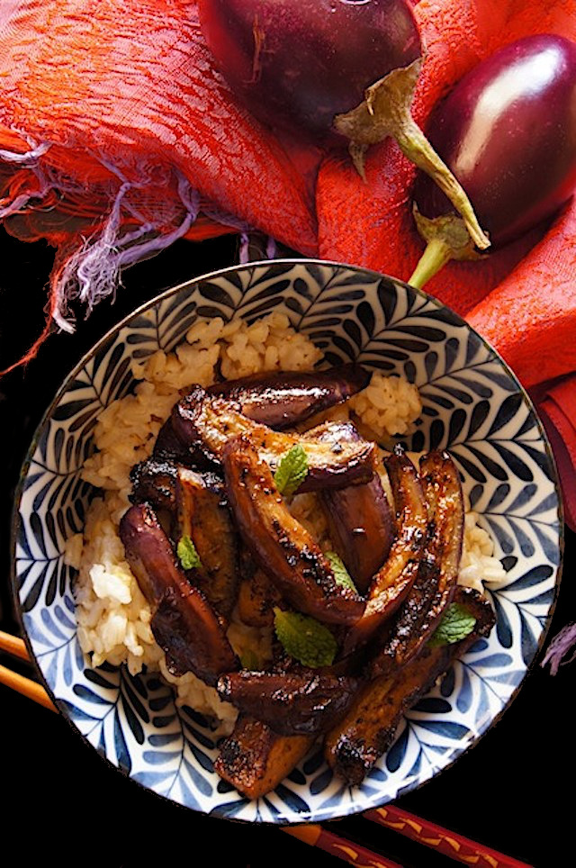 Spicy Miso Glazed Eggplant over brown rice in a blue and white bowl.