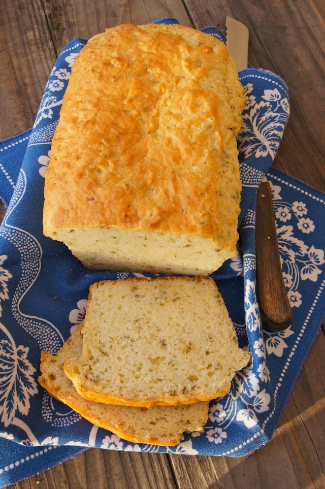 Herbed Garlic Bread partially sliced on a bright blue cloth napkin with a serrated knife