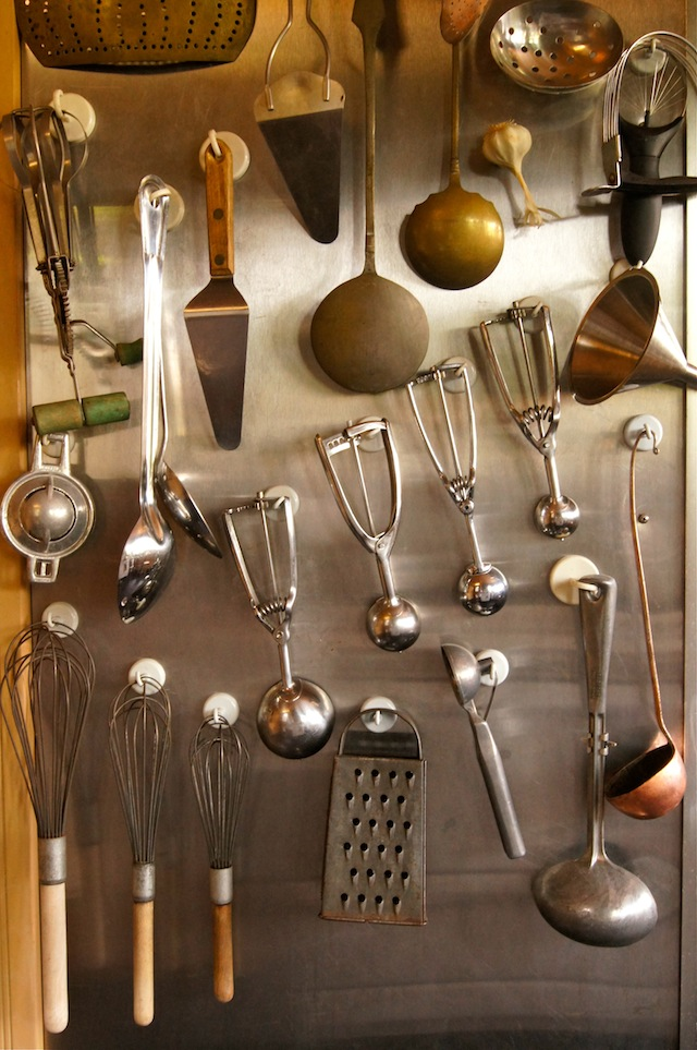 Collection of ice cream scoops hanging on stainless steel wall.
