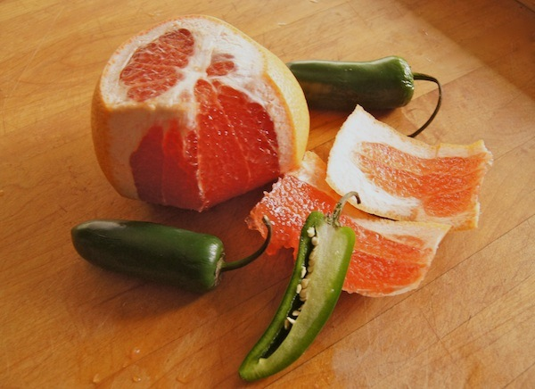 partially peeled grapefruit with sliced jalapenos on wood surface