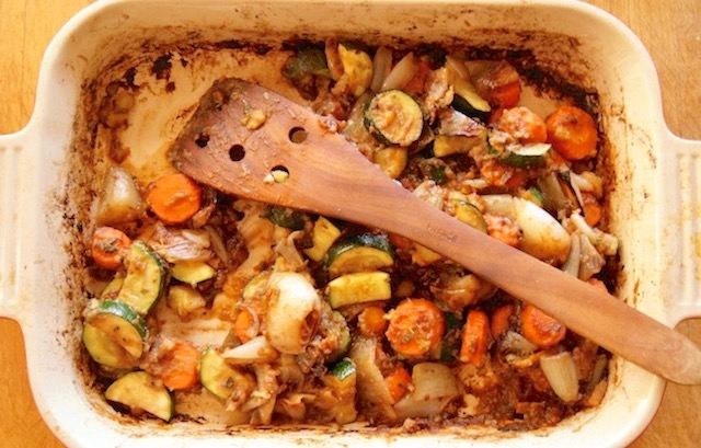 Roasted vegetables in baking pan with wooden spatula