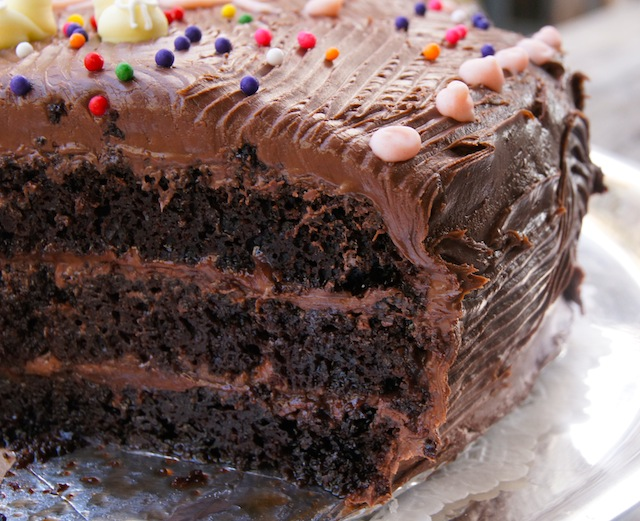 Close up shot of a large portion of Chocolate Blackout Nutella Cake with bits of colorful sprinkles on it.