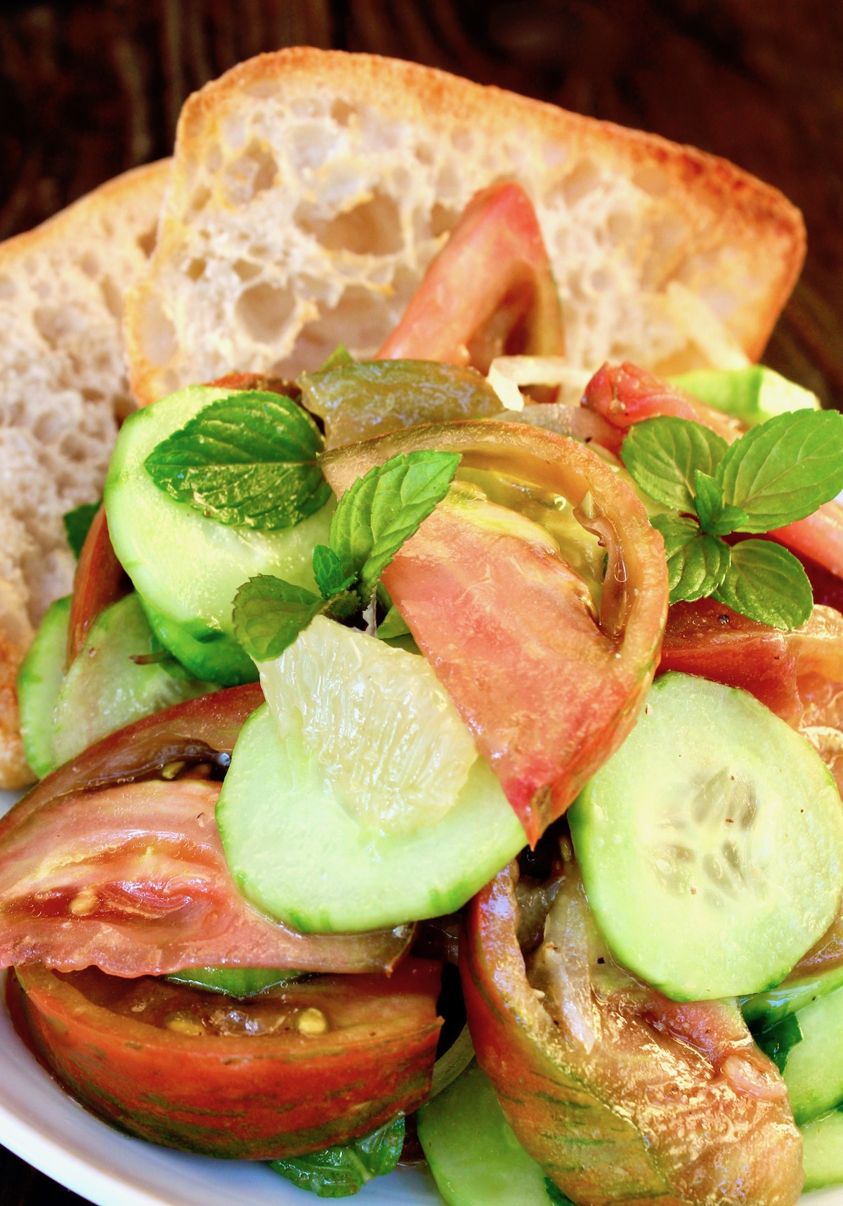 Close up of tomato and cucumber salad with slices of toast