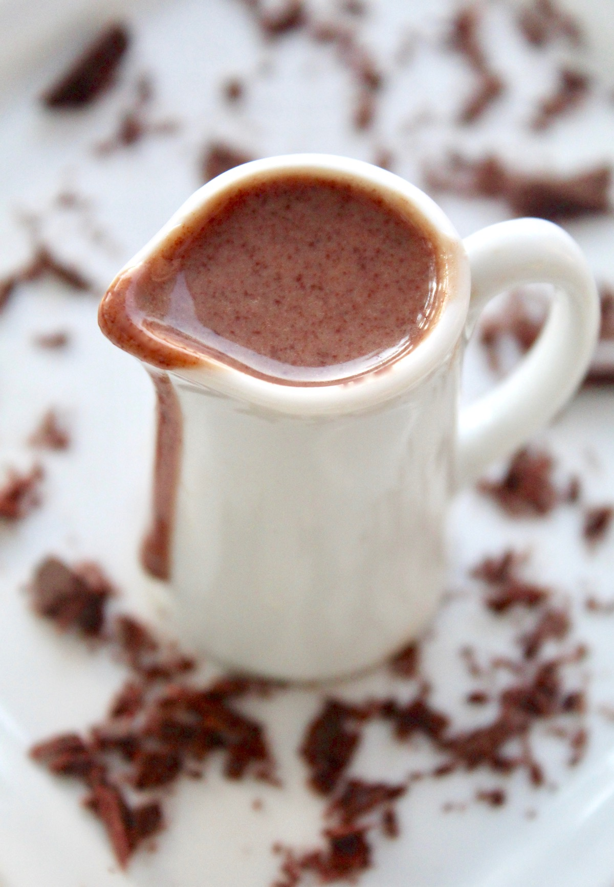 Chocolate dessert sauce dripping on the side of a white pitcher