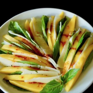 Mango Manchego Basil Salad on a white plate with title printed at the top.
