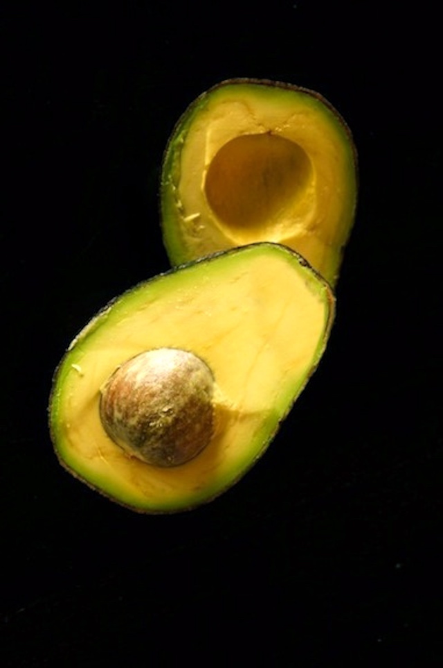 Avocado sliced in half with pit inside, black background