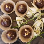 Several Biscoff Chocolate Truffles with white flowers between them