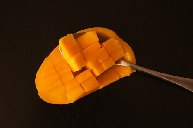 diced half of a mango with spoon