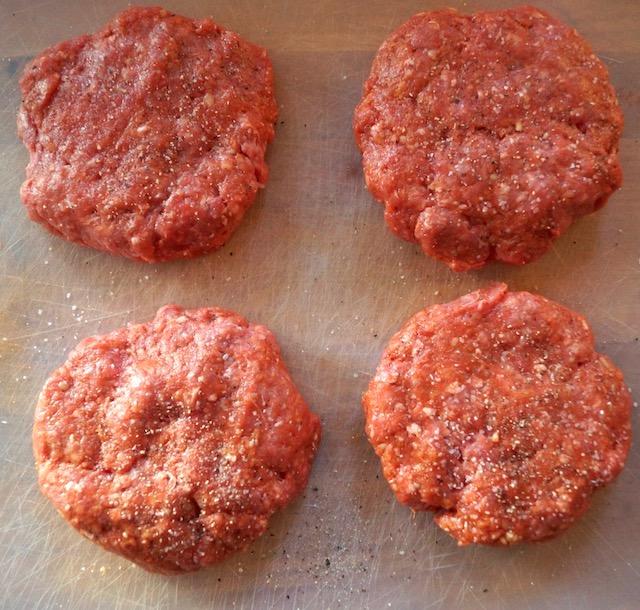 4 raw spicy sriracha burger patties on cutting board