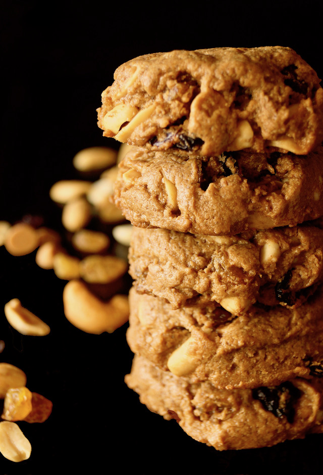 Tall stack of Trail MIx Peanut Butter Cookies with black background with a few nuts.