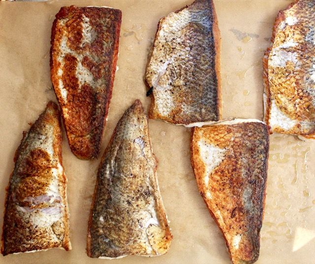 Browned Whitefish fillets, skin side up on parchment paper