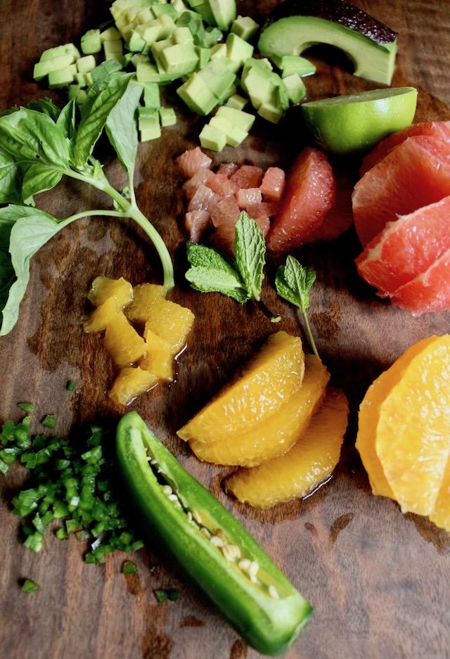 Ingredients on dark cutting board for citrus avocado salsa