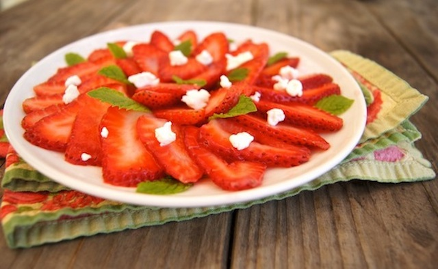 Fruit Carpaccio with Minty Strawberries on a white plate with goat cheese and mint leaves