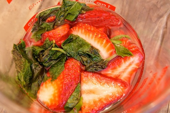 Strawberries marinating in mint wyrup in a clear measuing pitcher