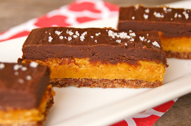 3 Peanut Butter Chocolate Decadence Bars on a white plate.
