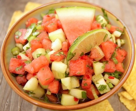 Watermelon Cucumber Salsa on a brown rimmed bowl with a watermelon and lime wedge.