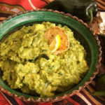 Roasted Poblano Guacamole in a green bowl with a striped tablecloth beneath it