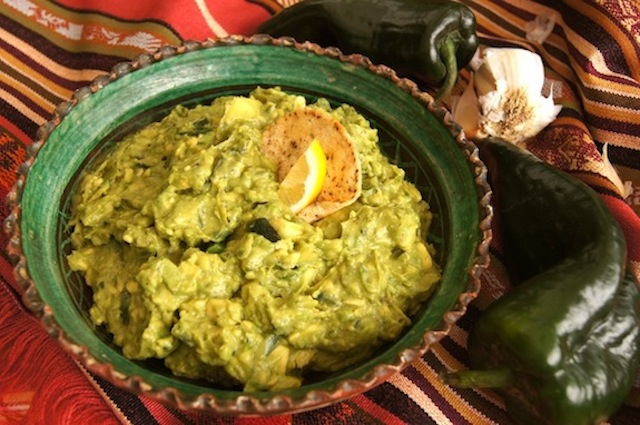 Poblano Guacamole in a green bowl on a rust-colored, striped, Mexican-styled tablecloth.