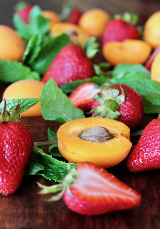 apricots, mint and strawberries on wood cutting board