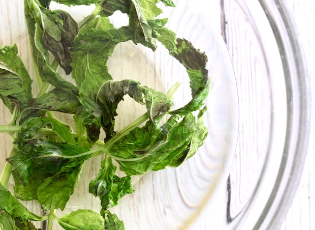 mint simple syrup in clear bowl