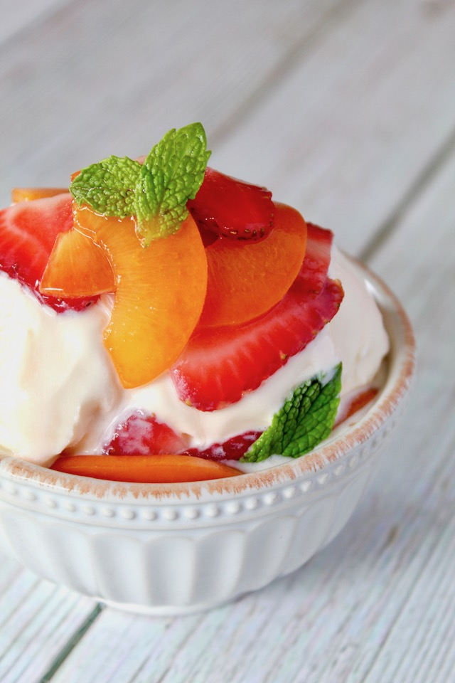 minty strawberries and spricots over vanilla ice cream in white bowl