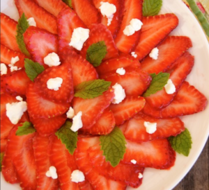 Strawberries sliced thinly on a white plate with mint