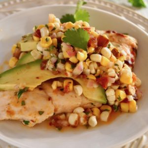Sheet Pan Chipotle Chicken with Corn Salsa on a white plate with avocado and cilantro sprigs