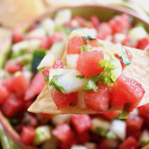 Close up of Watermelon Cucumber Salsa on a chip and in a bowl below it