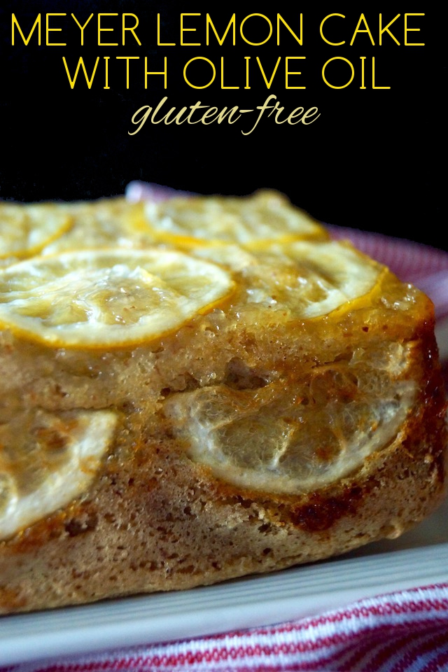 Unsliced half of Gluten-Free Meyer Lemon Cake with Olive Oil on a white plate with title in yellow at the top.