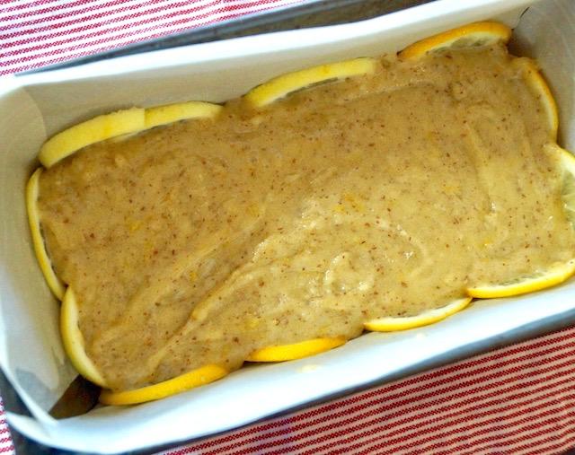 Lemons and cake batter inside parchment-lined loaf pan.