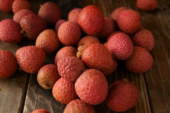 pile of lychees on wooden table