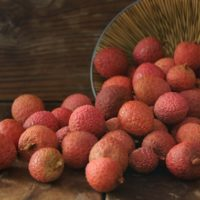 fresh lychee being poured out of a bowl with wood background