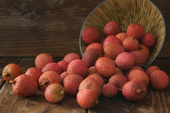 pile of lychees spilling out of a bowl