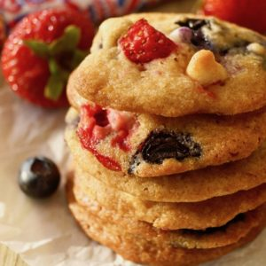 Stack of 6 Strawberry-Blueberry White Chocolate Chip cookies with a few blueberries and strawberries in background.